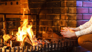 Human warming hands up at fireplace. Winter home.
